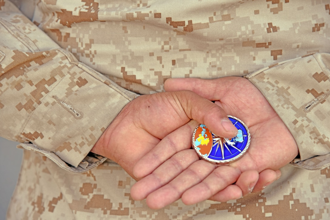 A 9th Air Expeditionary Task Force-Levant Marine holds an U.S. Air Forces Central Command's Commander coin, at the 407th Air Expeditionary Group in Southwest Asia, Dec. 14, 2017. U.S. Air Force Lt. Gen. Jeffery Harrigian, U.S. Air Forces Central Command Commander, gave the Marine the coin for being one of the 407th Air Expeditionary Group's top performers. (U.S. Air Force photo by Staff Sgt. Joshua Edwards/Released)