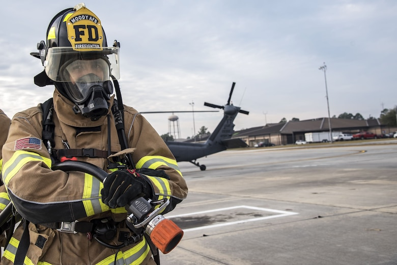 A firefighter from the 23d Civil Engineer Squadron (CES) holds a fire hose, Dec. 15, 2017, at Moody Air Force Base, Ga.  Members from the 723d Aircraft Maintenance Squadron (AMXS) and 23d Civil Engineer Squadron (CES) participated in a training day to help improve their readiness and get extra practice at their crafts. The AMXS performed maintenance on helicopters and the CES conducted rescue operations by extinguishing a mock fire within an HH-60G Pave Hawk and extracting injured victims. (U.S. Air Force photo by Airman Eugene Oliver)