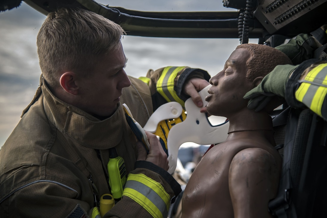 Airman 1st Class Austin Taylor, 23d Civil Engineer Squadron (CES) firefighter, applies a neck brace to a mannequin, Dec. 15, 2017, at Moody Air Force Base, Ga. Members from the 723d Aircraft Maintenance Squadron (AMXS) and 23d Civil Engineer Squadron (CES) participated in a training day to help improve their readiness and get extra practice at their crafts. The AMXS performed maintenance on helicopters and the CES conducted rescue operations by extinguishing a mock fire within an HH-60G Pave Hawk and extracting injured victims. (U.S. Air Force photo by Airman Eugene Oliver)