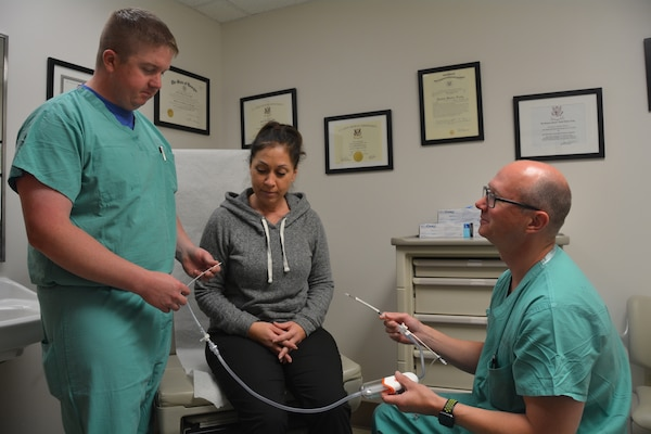 Army Lt. Col. (Dr.) Shane McEntire, a vascular surgeon at Brooke Army Medical Center, shows the device used to perform the TransCarotid Artery Revascularization procedure to Air Force Maj. (Dr.) William Harris, vascular surgeon, and DeAnn Yanez, a nurse in the vascular surgery clinic, Dec. 12, 2017. Surgeons must be specially trained or assisted by someone who has been trained on the device used during the TCAR procedure before they can do this surgery.