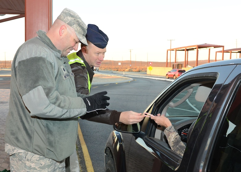 Lt. Col. Grant Vineyard, 412th Mission Support Group (left), and Lt. Col. Cory Naddy, 412th Test Wing Safety Office, greet motorists at the North Gate Dec. 18. A yearly tradition, base leadership and supervisors hand out candy canes and holiday cards at all of Edwards AFB's entry gates to show their appreciation to the Edwards workforce and wish everyone a safe holiday season. (U.S. Air Force photo by Kenji Thuloweit)