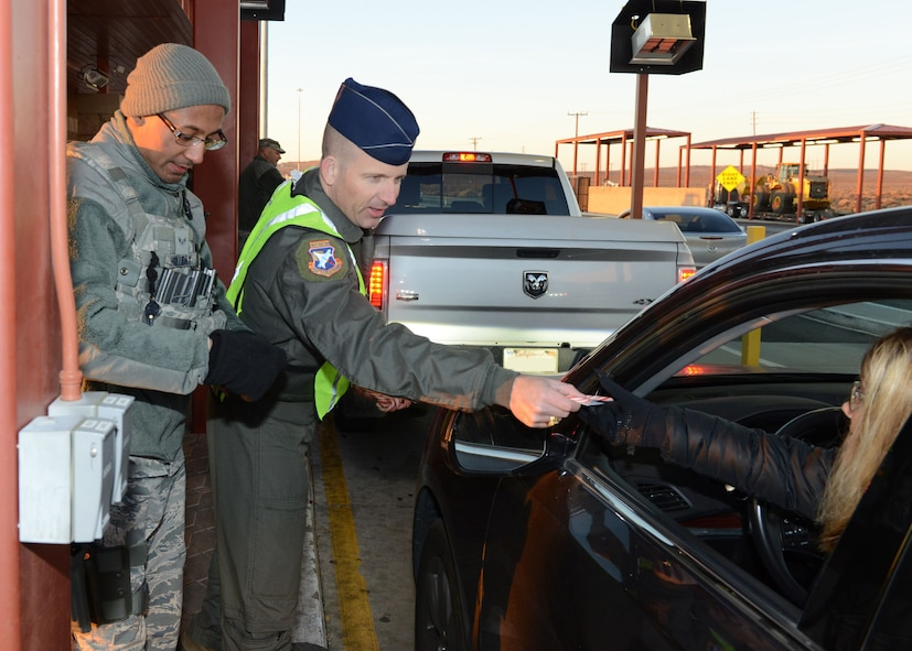 Col. Matthew Higer, U.S. Air Force Test Pilot School commandant, hands a candy cane and holiday card to a motorist at Edwards AFB's North Gate Dec. 18. The colonel teamed up with Airman 1st Class Jerome Holliday, 412th Security Forces Squadron, for the morning. (U.S. Air Force photo by Kenji Thuloweit)