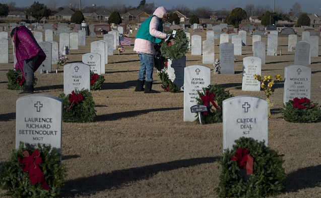 Volunteers from the local community place wreaths on veterans' graves during a Wreaths Across America ceremony at the Altus Cemetery, Okla., Dec. 16, 2017.