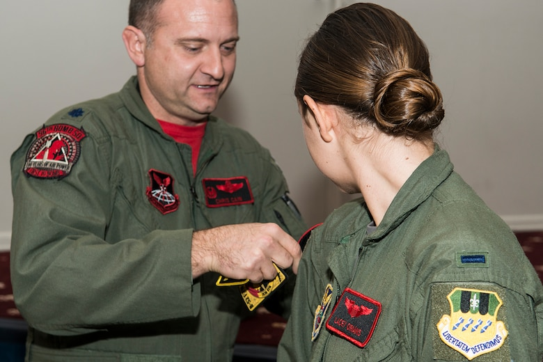 U.S. Air Force Lt. Col. Chris Cain, 96th Bomb Squadron commander, presents a patch to 1st Lt. Lacey Orians during the graduation of the Formal Training Unit class 17-02 on Barksdale Air Force Base, La. December 15, 2017.