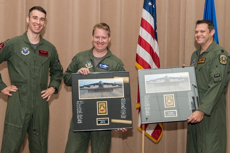 U.S. Air Force Capt. Anthony Mitchell presents class photos to Lt. Col. Brian Bailey, 93rd Bomb Squadron commander, and Lt. Col. William Fish, 11th BS commander, during a graduation ceremony for Formal Training Unit class 17-02 on Barksdale Air Force Base, La. December 15, 2017.