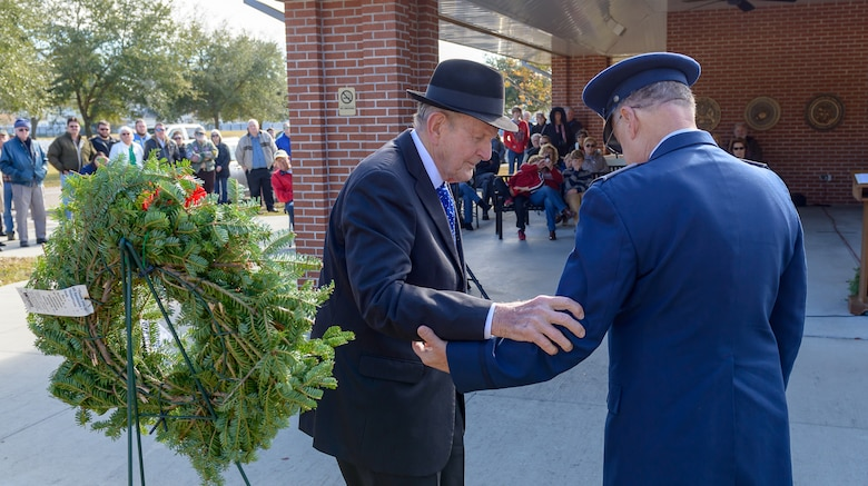 "Col. David ""Hank"" Rogers, Civil Air Patrol commander, assists Victor Mavar, U.S. Merchant Marine and Korean War veteran, during the Wreaths Across America ceremony at the Biloxi National Cemetery Dec. 16, 2017, in Biloxi, Mississippi. Wreaths Across America, a non-profit organization, was formed as an extension of the Arlington Wreath Project. The Arlington Wreath program was started by Morrill Worcester in 1992 with the donation and laying of 5000 Christmas wreaths to Arlington National Cemetery. (U.S. Air Force photo by André Askew)"