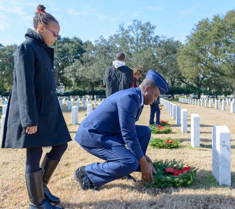 Col. Leo Lawson, Jr., 81st Training Group commander, lays a wreath as his daughter, Mia, looks on during the Wreaths Across America ceremony at the Biloxi National Cemetery Dec. 16, 2017, in Biloxi, Mississippi. Wreaths Across America, a non-profit organization, was formed as an extension of the Arlington Wreath Project. The Arlington Wreath program was started by Morrill Worcester in 1992 with the donation and laying of 5000 Christmas wreaths to Arlington National Cemetery. (U.S. Air Force photo by André Askew)
