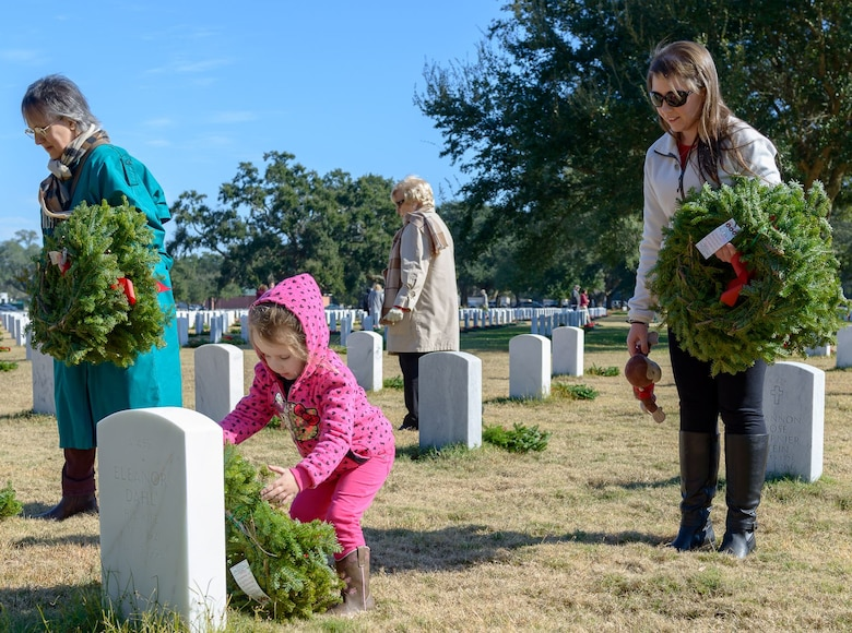 Senior Airman Holly Mansfield, 81st Training Wing photojournalist, watches her daughter, Abbey, lay a wreath during the Wreaths Across America ceremony at the Biloxi National Cemetery Dec. 16, 2017, in Biloxi, Mississippi. Wreaths Across America, a non-profit organization, was formed as an extension of the Arlington Wreath Project. The Arlington Wreath program was started by Morrill Worcester in 1992 with the donation and laying of 5000 Christmas wreaths to Arlington National Cemetery. Keesler leadership attended the event. (U.S. Air Force photo by André Askew)