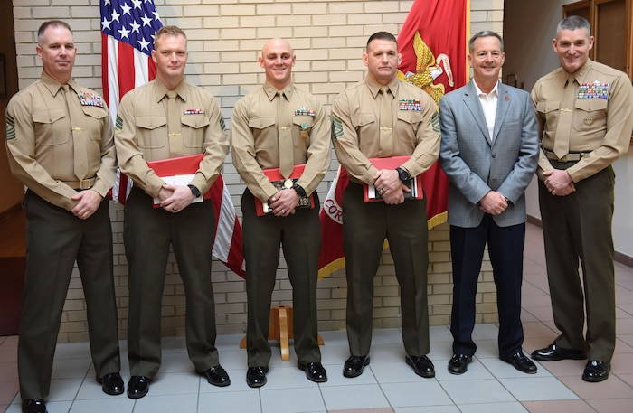 Brig. Gen. Jason Bohm, (Far right), Sgt. Maj. Jeffrey Monssen (Far left) and retired Lt. Gen. William Faulkner pose with the winners of the Training Command's Commanding General's Writing Competition at Marine Corps Base Quantice, Virginia, Dec. 14, 2017. Capt. Kyle Tucker-Davis, GySgt. William Callen and Sgt. Matthew Harrison, won 1st, 2nd and 3rd place, respectively. Bohm is the commanding general for Training Command. Monssen is the Sergeant Major for Training Command.