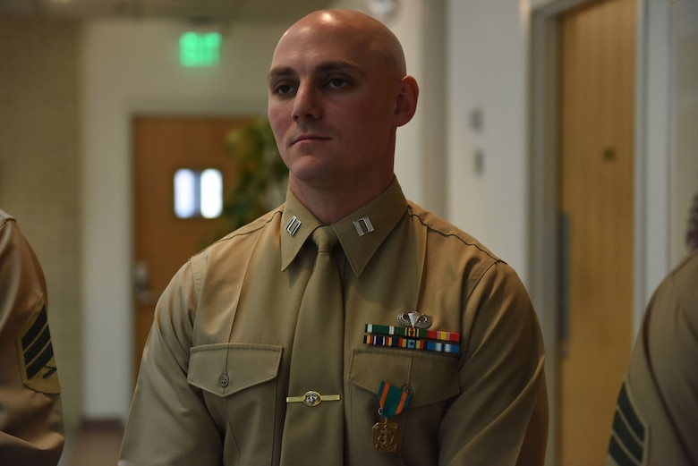 """Capt. Kyle Tucker-Davis stands with his Navy-Marine Corps Achievement Medal during the award ceremony for the Training Command's Commanding General's Writing Competition at Marine Corps Base Quantice, Virginia, Dec. 14, 2017. Capt. Kyle Tucker-Davis, a warfighting instructor at The Basic School, took lst first place for his essay on Russian affairs, titled """"New Generation Warfare: An Analysis of Russian Operations in Ukraine and Implications for the Future of U.S. Joint Operation."""""""