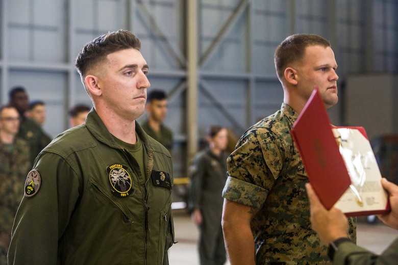 """Sgt. Ethan Mintus and Sgt. Joseph Latsch, both unmanned aerial system operators with Marine Unmanned Aerial Vehicle Squadron 3, wait to be awarded during a ceremony at Hangar 103, Marine Corps Air Station Kaneohe Bay, Dec. 11, 2017. They were awarded the Navy and Marine Corps Achievement Medal with the newly authorized Remote Impact """"R"""" Device for their performance during combat operations."""