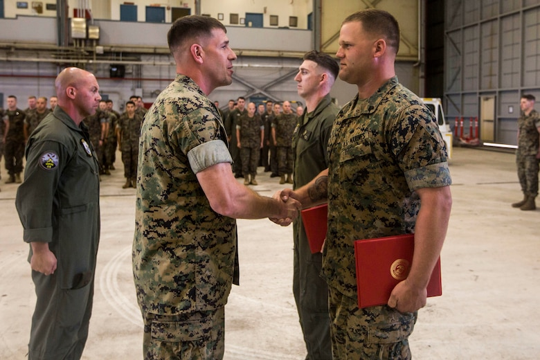 """Sgt. Ethan Mintus, an unmanned aerial system operator with Marine Unmanned Aerial Vehicle Squadron 3, shakes hands with Lt. Col. Kenneth Phelps, the commanding officer of VMU-3, after receiving an award during a ceremony at Hangar 103, Marine Corps Air Station Kaneohe Bay, Dec. 11, 2017. Mintus was awarded the Navy and Marine Corps Achievement Medal with the newly authorized Remote Impact """"R"""" Device alongside Sgt. Joseph Latsch, a fellow UAS operator with VMU-3, for their performance during combat operations."""