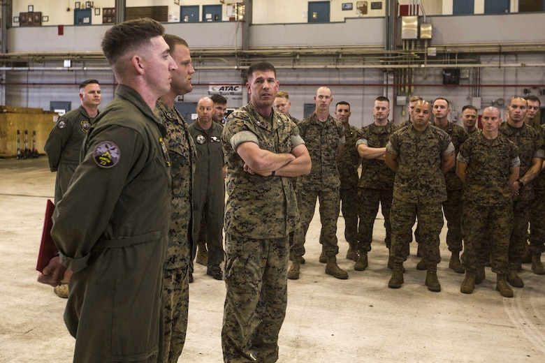 """Lt. Col. Kenneth Phelps, the commanding officer of Marine Unmanned Aerial Vehicle Squadron 3, recognizes Sgt. Joseph Latsch and Sgt. Ethan Mintus, unmanned aerial system operators with VMU-3, after an award ceremony at Hangar 103, Marine Corps Air Station Kaneohe Bay, Dec. 11, 2017. Latsch and Mintus are the first UAS operators in the Marine Corps to receive a Navy and Marine Corps Achievement Medal with the newly authorized Remote Impact """"R"""" Device for providing support during combat operations."""