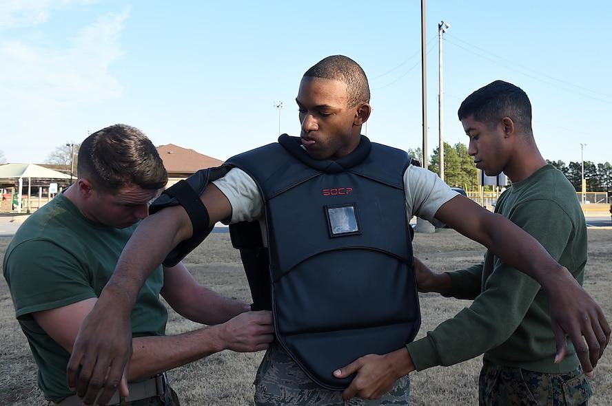 Three Marines put on protective gear before pugil stick match.