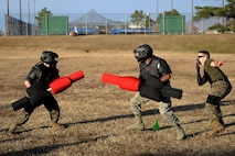 A Marine and an Airman engaged in a pugil stick match.