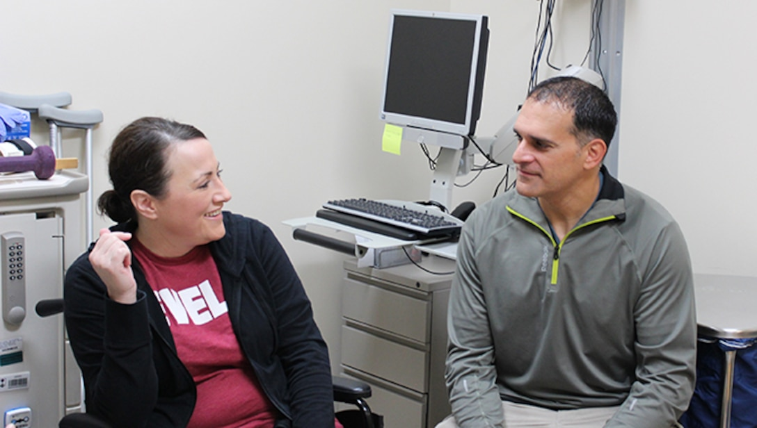 U.S. Air Force Maj. Stephanie Proellochs discusses her treatment journey with her husband, John at Walter Reed Medical Center, Nov. 8, 2017. Proellochs explains how her husband's experience working with amputees prepared her for her own procedure. (U.S. Air Force photo by Karina Luis)