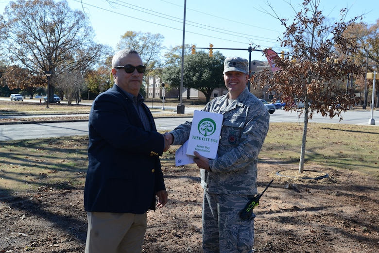 U.S. Air Force Lt. Col. Robert Grover, 20th Civil Engineer Squadron (CES) commander, accepts the Tree City USA award from Everett Sharpe, South Carolina Forestry Commission urban forester, at Shaw Air Force Base, S.C., Dec. 13, 2017.