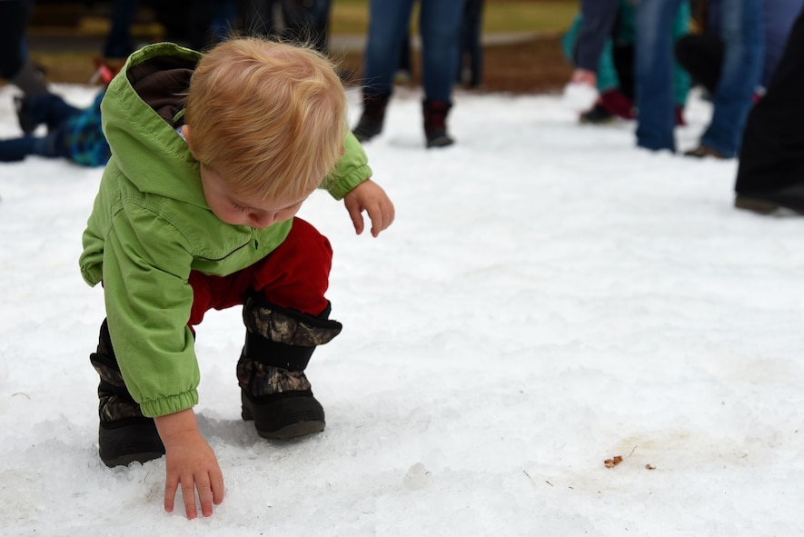 A Team Shaw child touches snow during the 20th Force Support Squadron's Frosty Fest at Shaw Air Force Base, S.C., Dec. 17, 2017.