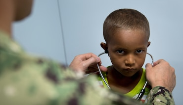 Doctor puts a stethoscope on a Brazilian boy.