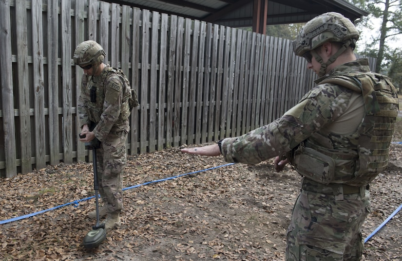 1st Lt. Paul Underwood, searches for mines SrA Koser, Matthew Civil Engineer Squadron Explosive Ordnance Disposal technician searches for mines while Senior Airman Matthew Koser, 628th CES EOD technician instructs him on proper techniques during the EOD Olympics Dec. 15, 2017.
