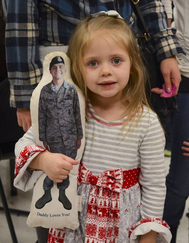 Adalyn Deryke, daughter of Brandon Deryke, 822d Base Defense Squadron NCO in charge of combat arms, poses for a photo during a holiday party with a pillow displaying her father's picture, Dec. 15, 2017, at Moody Air Force Base, Ga. The Airman and Family Readiness Center hosted the event for families of deployed or remote-tour Airmen, and families enrolled in the Exceptional Family Member Program. During the party, families enjoyed a turkey dinner, played games, made arts and crafts for their loved ones and shared a special moment with Santa Claus. (U.S. Air Force photo by Senior Airman Lauren M. Sprunk)