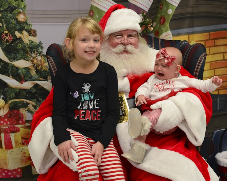 Reagan and Meredith, daughters of Senior Airman Michael Verheyden, 74th Aircraft Maintenance Unit crew chief, pose for a photo with Santa during a holiday party, Dec. 15, 2017, at Moody Air Force Base, Ga. The Airman and Family Readiness Center hosted the event for families of deployed or remote-tour Airmen, and families enrolled in the Exceptional Family Member Program. During the party, families enjoyed a turkey dinner, played games, made arts and crafts for their loved ones and shared a special moment with Santa Claus. (U.S. Air Force photo by Senior Airman Lauren M. Sprunk)