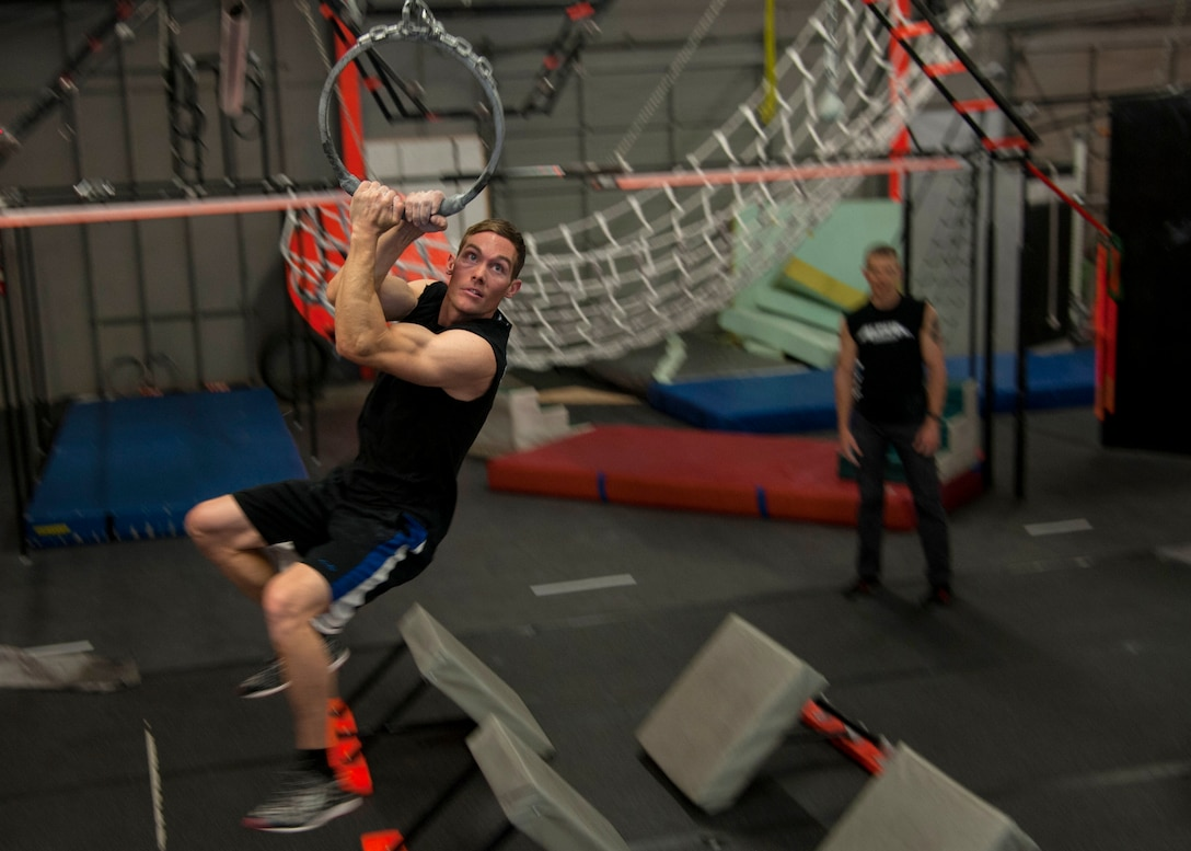 """Tech. Sgt. David Krause, 58th Maintenance Squadron CV-22 """"osprey"""" crew chief, swings on an obstacle at the Ninja Force Gym, Albuquerque, N.M., Dec. 4. Krause began his ninja obstacle training a year ago."""