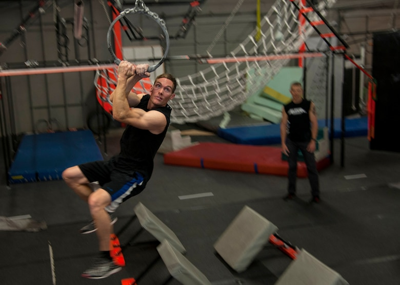 "Tech. Sgt. David Krause, 58th Maintenance Squadron CV-22 ""osprey"" crew chief, swings on an obstacle at the Ninja Force Gym, Albuquerque, N.M., Dec. 4. Krause began his ninja obstacle training a year ago."