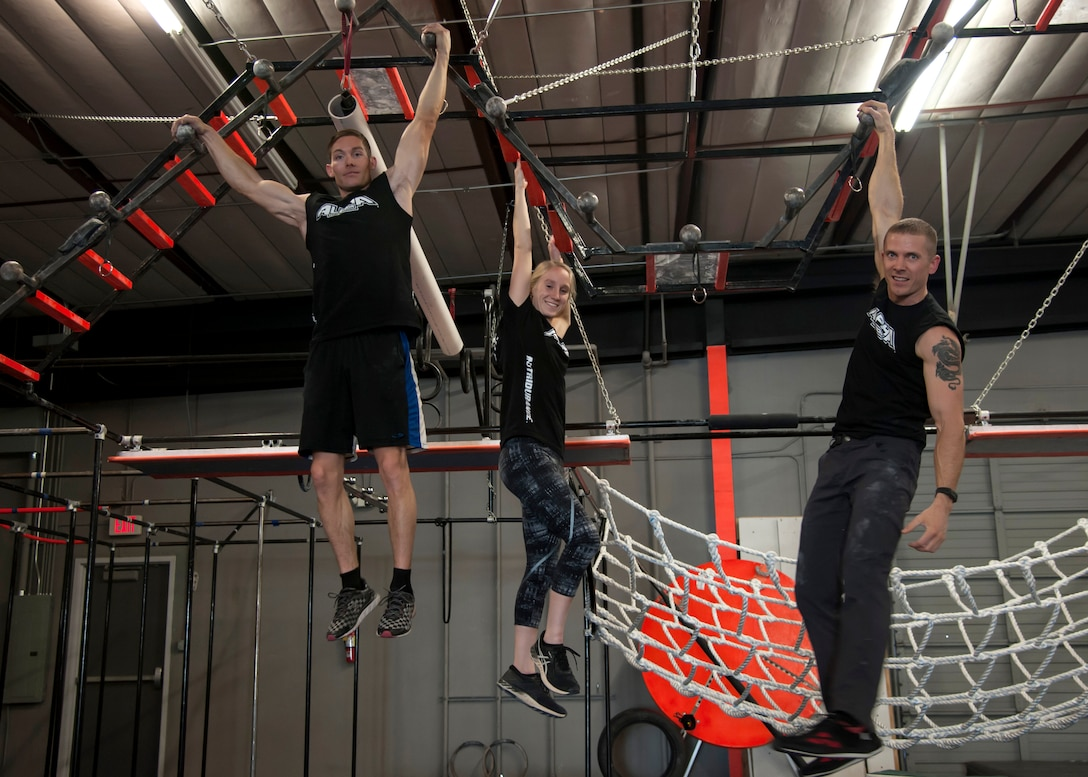 "2nd Lt. Zoe Casteel, Air Force Research Lab space systems engineer, Tech. Sgt. David Krause, 58th Maintenance Squadron CV-22 ""osprey"" crew chief, and 1st Lt. Eddie Hilburn, Air Force Research Lab optical physicist, work out at the Ninja Force Gym, Albuquerque, N.M., Dec. 4."