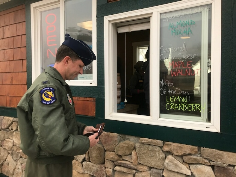 Col. Christopher Sage, 4th Fighter Wing commander, purchases the first drink at the newly opened coffee kiosk, Dec. 19, 2017, at Seymour Johnson Air Force Base, North Carolina. The coffe shop is open Monday thru Friday from 5:30 a.m. until noon. (U.S. Air Force photo by Airman 1st Class Shawna Keyes)