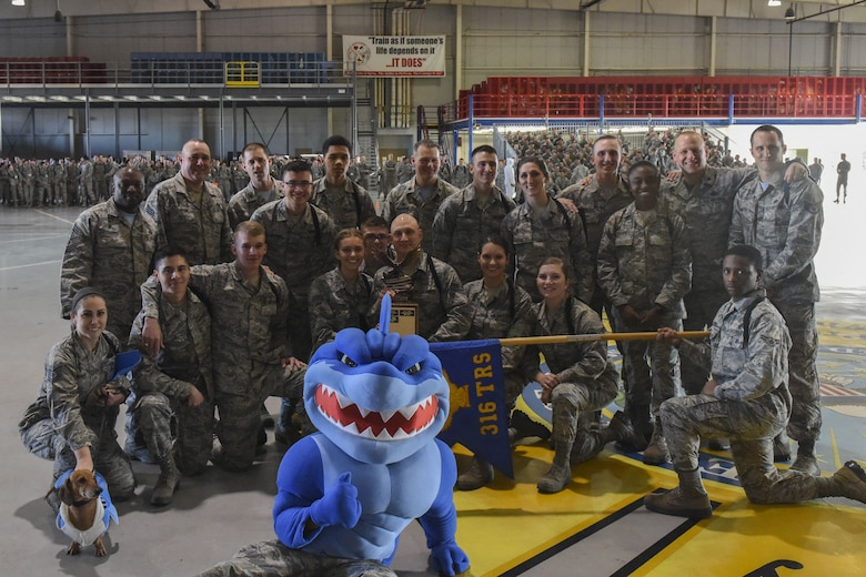 The 316th Training Squadron drill team poses with their trophy after winning each of the categories during the 17th Training Group drill competition at the Louis F. Garland Department of Defense Fire Academy on Goodfellow Air Force Base, Texas, Dec. 15, 2017. Leadership joined in the group photo along with the 316th TRS mascot and Gary the Dachshund. (U.S. Air Force Photo by Airman 1st Class Zachary Chapman/Released)
