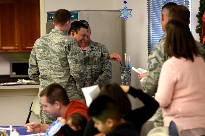 U.S. Air Force Maj. Mark Edelstein, 502nd Air Base Wing chaplain, assists Col. Jeffery Sorrell, 17th Training Wing vice commander, light one of the candles on the Menorah at Goodfellow Air Force Base, Texas, Dec. 15, 2017. Several families gathered to enjoy each other's company, worship and hear the story of Hanukkah at the Taylor Chapel. (U.S. Air Force photo by Airman 1st class Seraiah Hines/Released)