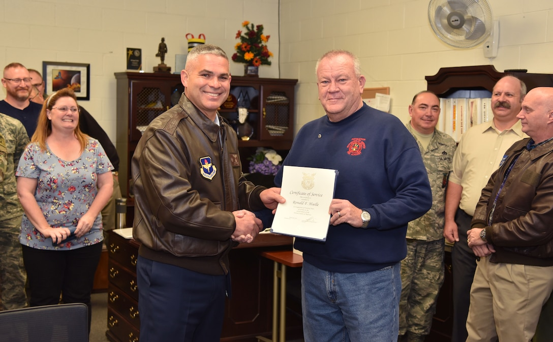 U.S. Air Force Col. Alejandro Ganster, 17th Training Group commander, presents a 20 year recognition certificate to Ronald Hoelle, 312th Training Squadron training developer, at Goodfellow Air Force Base, Dec. 7, 2017. Hoelle has been working with the 17th TRG for the entirety of his career as a civilian. (U.S. Air Force photo by Russell Stewart/Released)