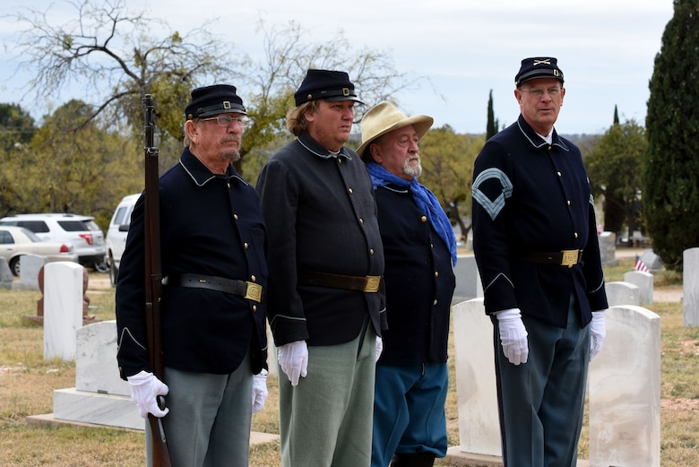 Volunteers from Fort Concho stand at attention in traditional clothing during the Wreaths Across America ceremony, at Belvedere Memorial Park, San Angelo, Texas, Dec. 16, 2017. The ceremony is held at cemeteries across the world in remembrance to those who have served our country. (U.S. Air Force photo by Airman 1st Class Seraiah Hines/Released)