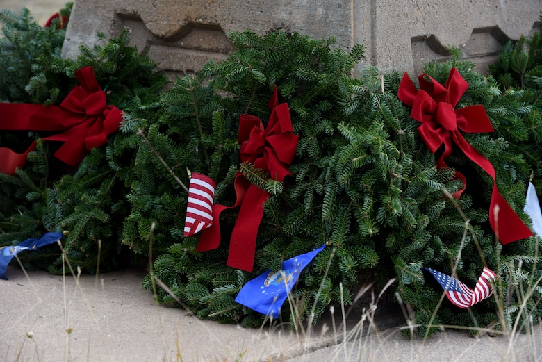 Symbolic wreaths are laid at the base of the flag in Belvedere Memorial Park, San Angelo, Texas, Dec. 16, 2017. One wreath per branch and a POW/MIA wreath was laid at the base of the flagpole during the Wreaths Across America Ceremony. (U.S. Air Force photo by Airman 1st Class Seraiah Hines/Released)