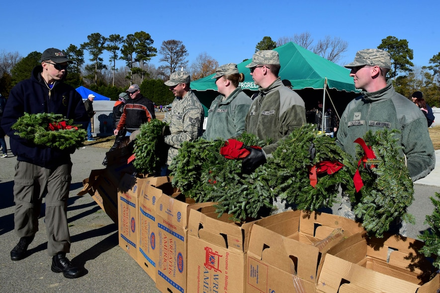Members of the 4th Fighter Wing hand out wreaths to be placed on the graves of fallen service members during the Wayne County Wreaths Across America ceremony Dec. 16, 2017, at Evergreen Memorial Cemetery in Princeton, North Carolina.