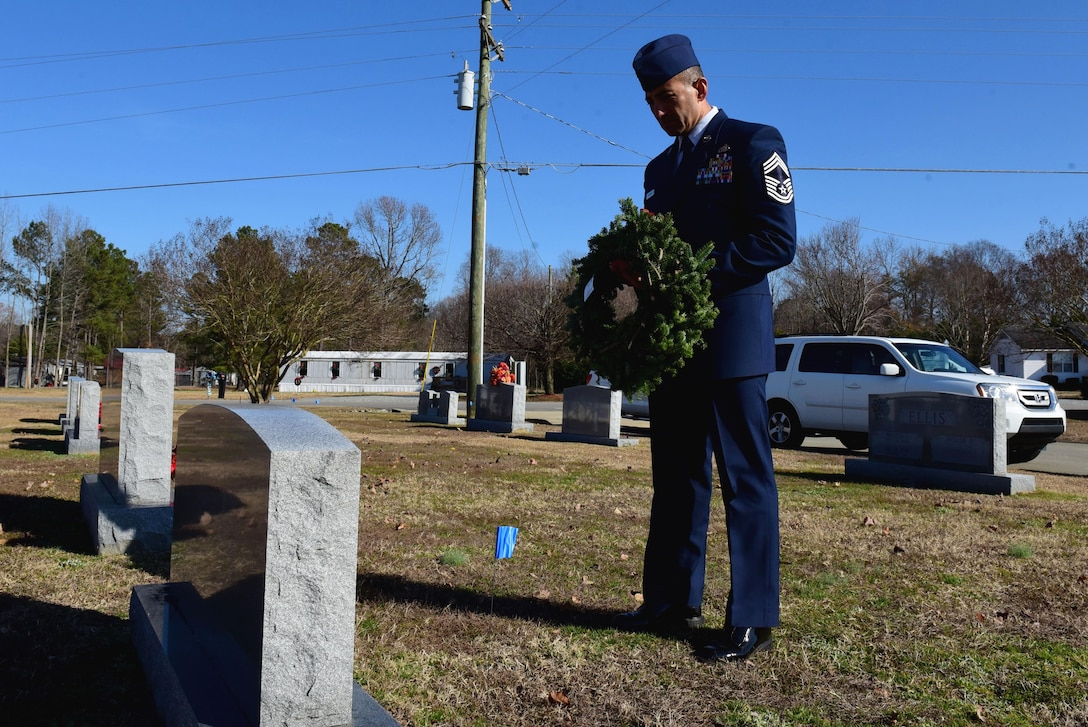 Chief Master Sgt. Marlon Carcamo, 4th Mission Support Group superintendent, lays a wreath on the grave of a fallen service member during the Wayne County Wreaths Across America ceremony Dec. 16, 2017, at Evergreen Memorial Cemetery in Princeton, North Carolina.