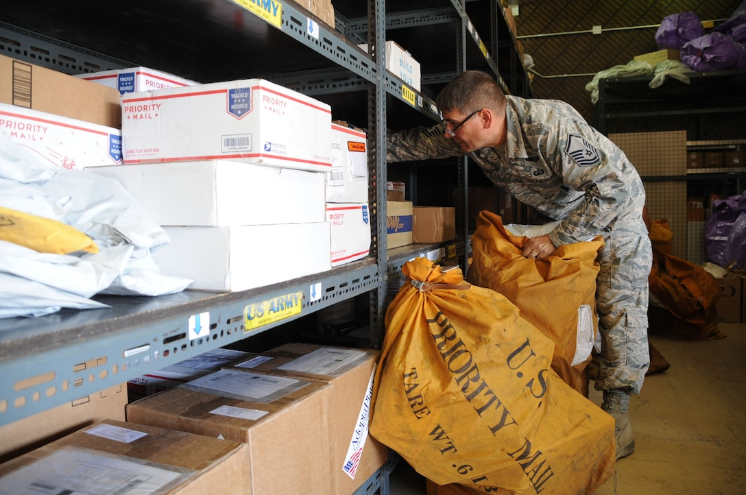 Volunteers from the 380th Air Expeditionary Wing, Al Dhafra Air Base, United Arab Emirates, work together sorting incoming packages at the post office Dec. 12, 2017. The daily parcel inbound average for the post office is 716. (U.S. Air National Guard photo by Staff Sgt. Colton Elliott)