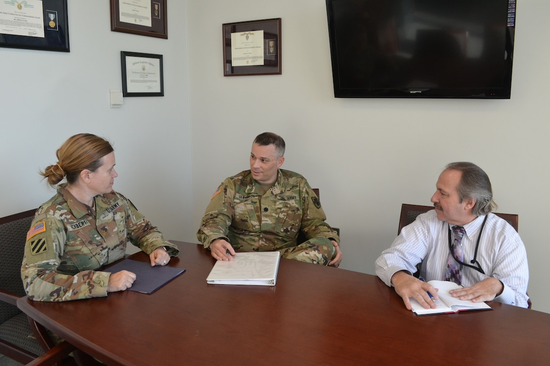 Army Reserve Lt. Col. Josh Van Eaton (center) meets with Army Maj. Heather Herbert (left) and Michael Lunceford (right), an administrative specialist  in the DLA Office of General Counsel. (Photo by Dianne Ryder.)