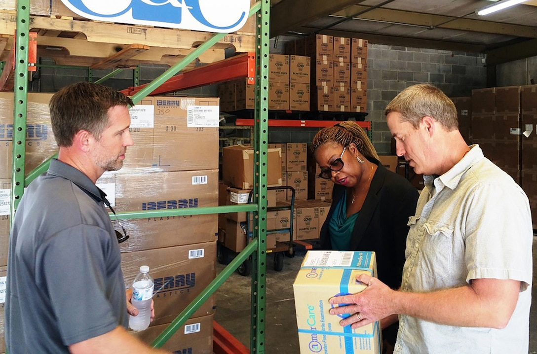 Jonathan Connell, CEO, and Todd Daughtry, COO, co-owners of veteran-owned small business C & C Containers, LLC meet in their Albany, Georgia, warehouse with Georgia PTAC Procurement Counselor Bridget Bennett to discuss product packaging and marking requirements for shipment of medical supplies.