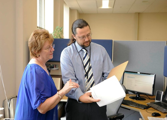 Robert Steed, a contracting officer for DLA Disposition Services, discusses a new contract with Sheryl Woods, DLA Disposition Services' special assistant for small business.