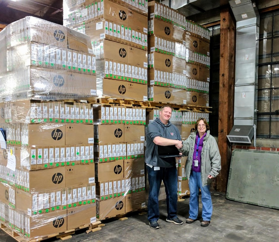 District Technology Supervisor Ryan Stockton of Ohio's Minford Local School District shakes the hand of DLA Disposition Services Property Disposal Specialist Cindy Anderson as he prepares to load up 1,300 excess laptops that no longer met DoD security requirements.
