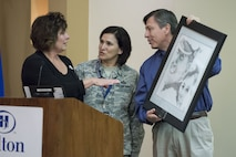 Col. Denise Cooper and Jerry Perez present a hand-drawn portrait to Janine Sijan-Rozina following her presentation at the Profession of Arms Center of Excellence Summit V, Dec. 6.