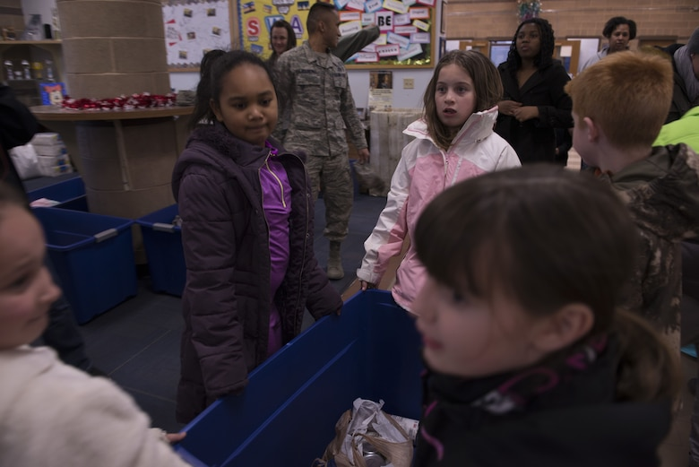 Children from the Youth Center's rainbow discovery clubhouse room help carry a donation tub to a vehicle Dec. 19, 2017, at Mountain Home Air Force Base, Idaho. The children at the Youth Center collected food items for two weeks to donate to the first sergeants food pantry. (U.S. Air Force photo by Senior Airman Lauren-Taylor Levin)
