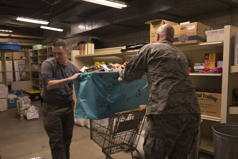 Master Sgt. Lucas Sanders, 366th Fighter Wing first sergeant, and Master Sgt. Phillip Horton, 266th Range Squadron first sergeant, roll in a food donation bin, Dec. 19, 2017, at Mountain Home Air Force Base, Idaho. The children at the Youth Center collected more than 250 food items. (U.S. Air Force photo by Senior Airman Lauren-Taylor Levin)