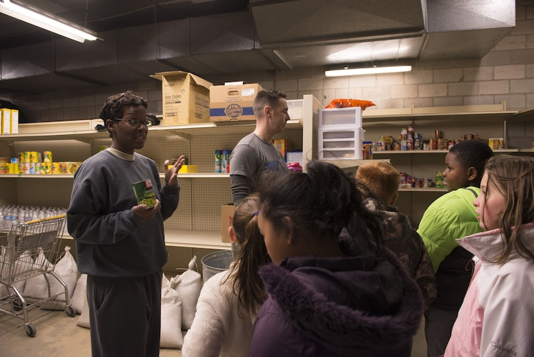 Senior Master Sgt. Makeba Liebert, 366th Medical Group first sergeant, explains where to put each food item to the Youth Center children, Dec. 19, 2017, at Mountain Home Air Force Base, Idaho. All items in the first sergeants food pantry go to base members in need of assistance. (U.S. Air Force photo by Senior Airman Lauren-Taylor Levin)