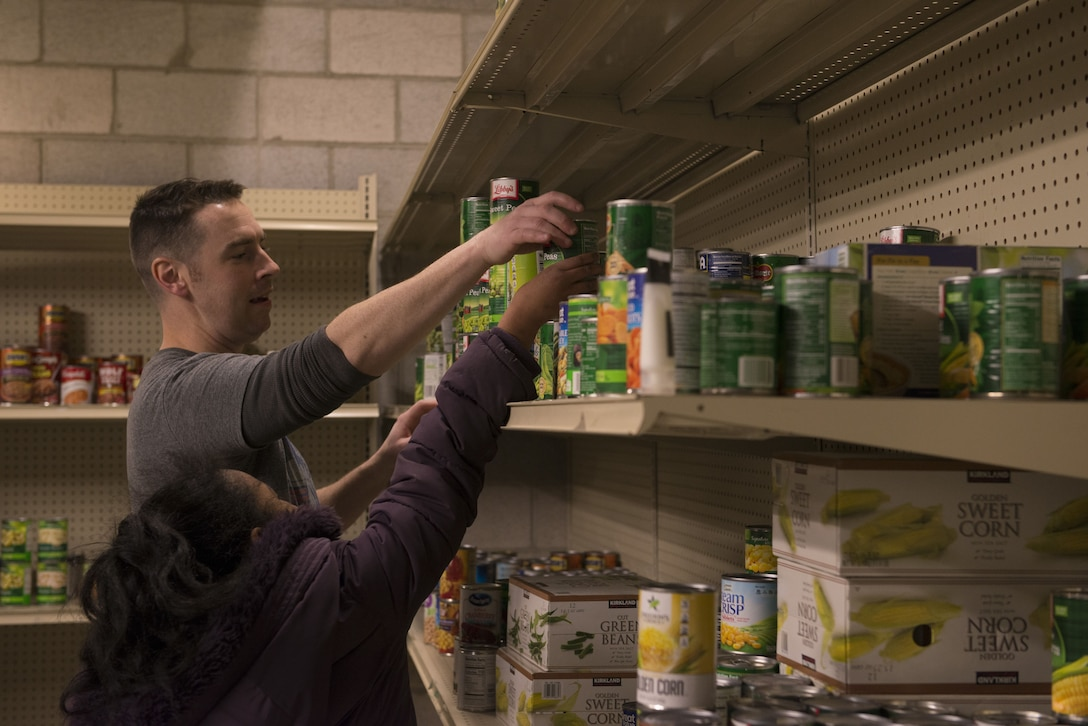 Master Sgt. Lucas Sanders, 366th Fighter Wing first sergeant, helps a child put a can of food on a shelf Dec. 19, 2017, at Mountain Home Air Force Base, Idaho. All items in the food pantry will assist base families in need year round. (U.S. Air Force photo by Senior Airman Lauren-Taylor Levin)