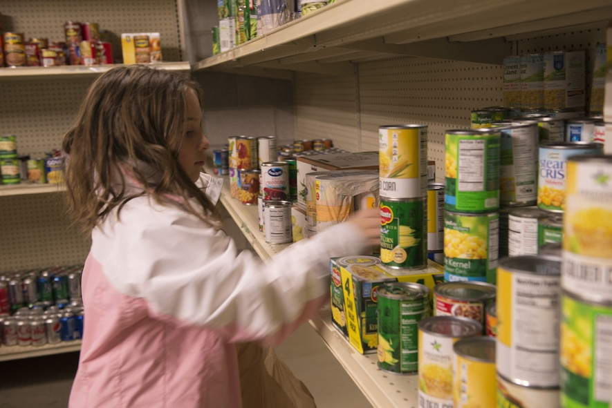 A child from the Youth Center places a can of food on a shelf Dec. 19, 2017, at the first sergeants food pantry. Children ages 6-18 donated non-perishable food items to help their community members during the holiday season. (U.S. Air Force photo by Senior Airman Lauren-Taylor Levin)