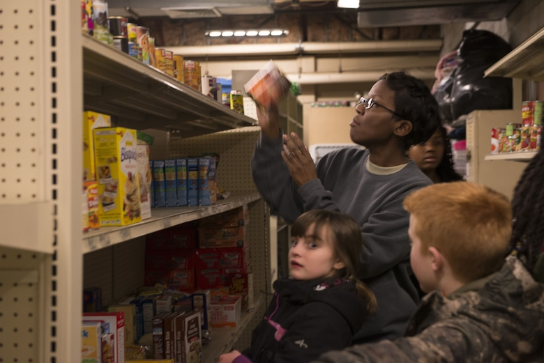 Senior Master Sgt. Makeba Liebert, 366th Medical Group first sergeant, helps put food items on a shelf Dec. 19, 2017 at Mountain Home Air Force Base, Idaho. The pre-teen group at the youth center came up with the idea to have a food drive after identifying some individuals didn't have enough food for the holiday. (U.S. Air Force photo by Senior Airman Lauren-Taylor Levin)