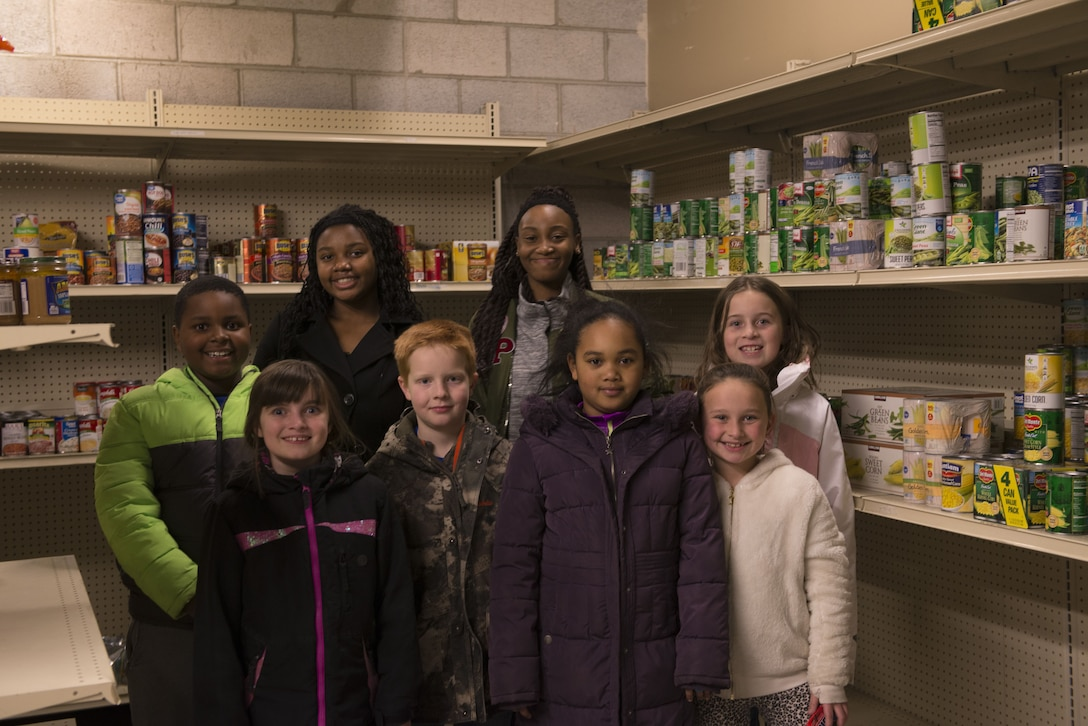 Members of the open recreation and rainbow discovery clubhouse room from the Youth Center pose for a group photo Dec. 19, 2017, at Mountain Home Air Force Base, Idaho. After the end of the food drive both groups came to help place the food items in the first sergeants food pantry. (U.S. Air Force photo by Senior Airman Lauren-Taylor Levin)